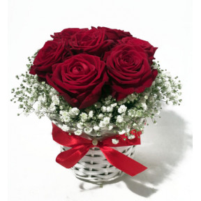 Arrangement of red roses in a small white basket